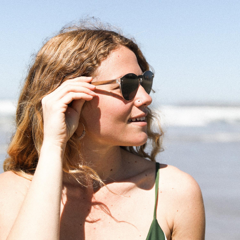 Round walnut wood sunglasses with black polarized one piece lens on women