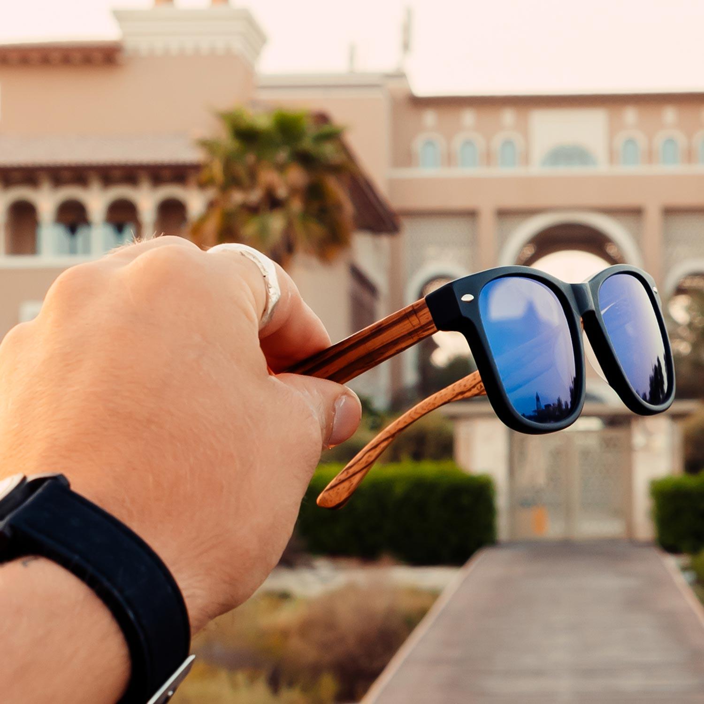 Zebra wood wayfarer sunglasses blue lenses outdoors